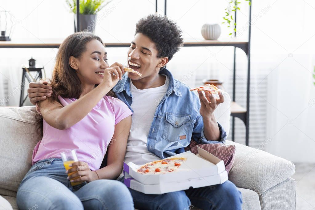 Lovely black teenage couple sharing pizza on date at home - Stock ...