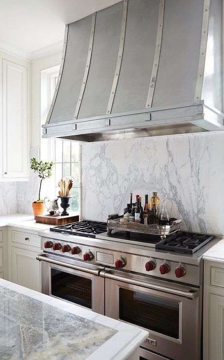 Zinc French Kitchen Hood Above A Marble Cooktop Backsplash And Wolf Range