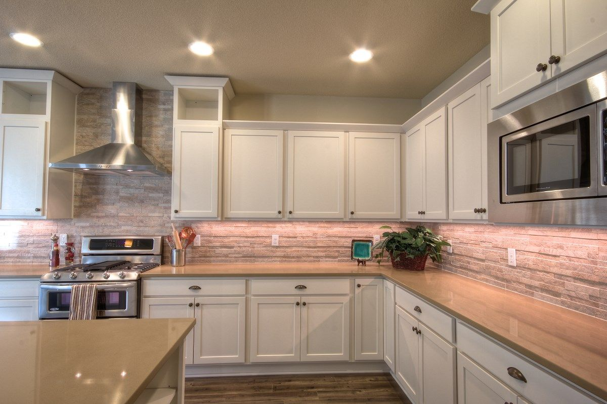 white kitchen cabinets with salmon color tile back splash and