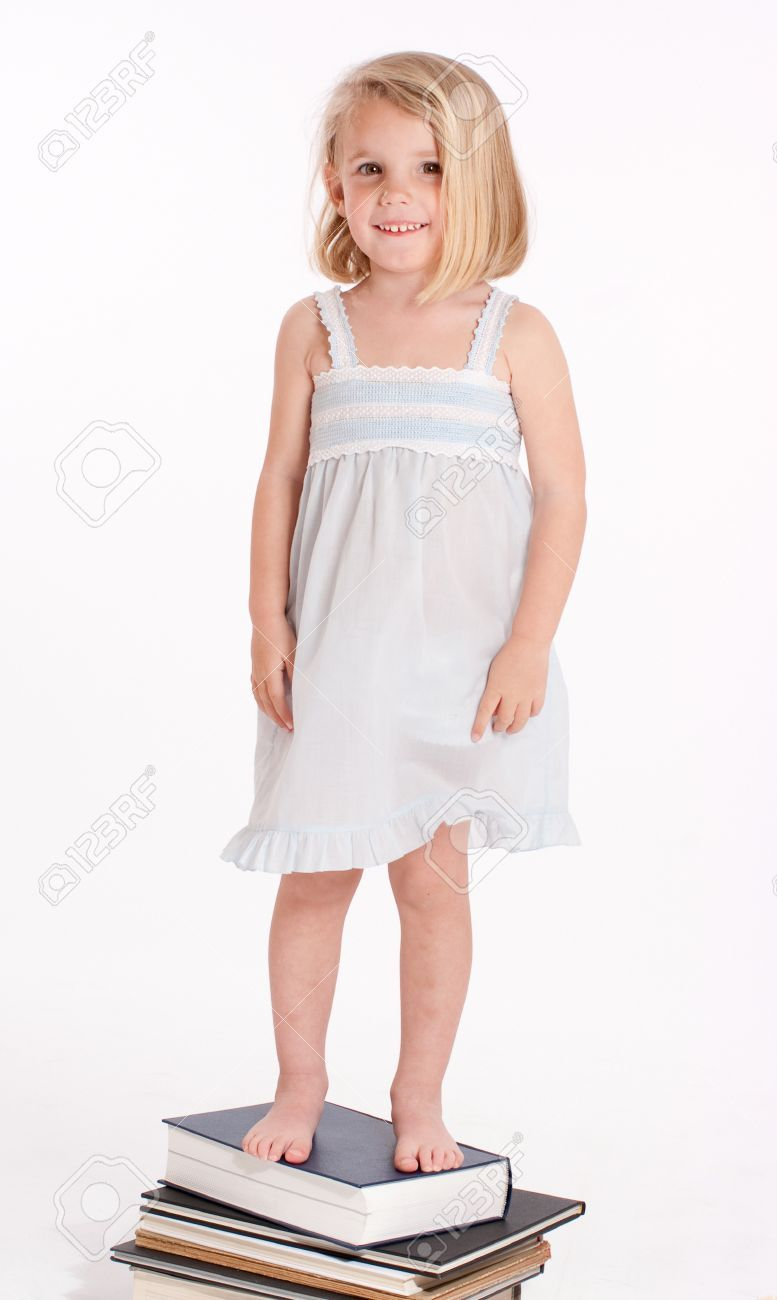 Little Girl In Her Nightgown Standing On A Pile Of Books Stock Photo ...