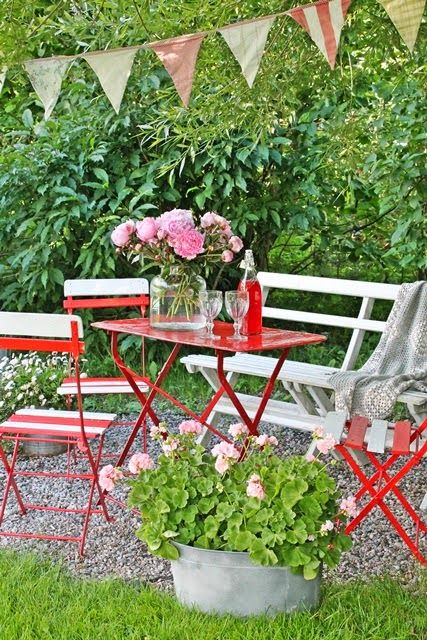 VIBEKE DESIGN  red table, welcoming bench, flowers, in the garden - this setting has it all!