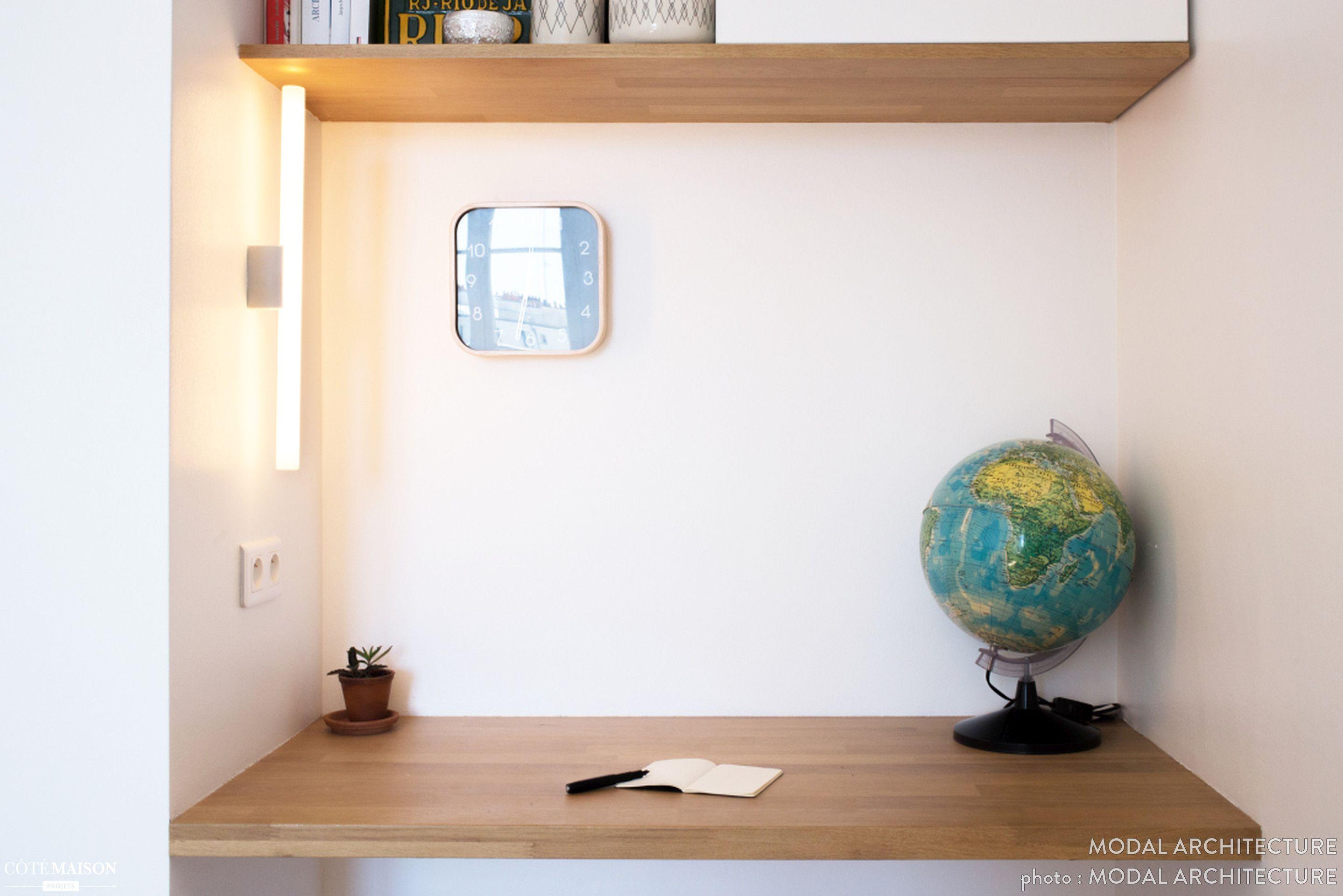 Petit coin bureau aménagé peu d élément déco hormis un globe