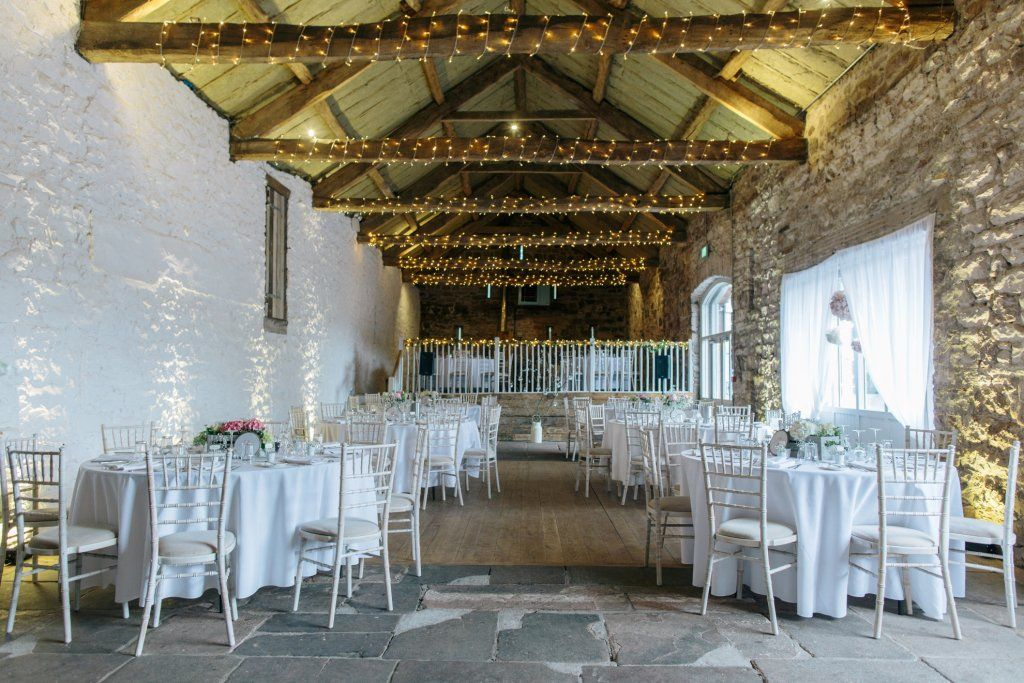 romantic twinkling fairy lights in the rustic barn at askham hall a wedding venue