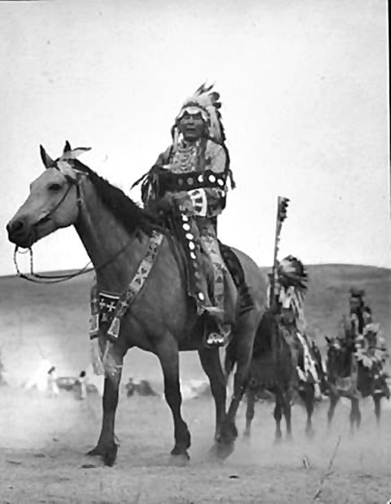 Colville men including Joe Moses wear ceremonial dress in procession on horseback, Washington Notes Three men on horseback ride in single file; in background can be seen tepees and people moving about. The two men in front wear feathered headdresses & beaded clothing, man in rear has roach headdress and carries a feathered shield. Lead horse has feathers in mane, and beaded breast collar .: