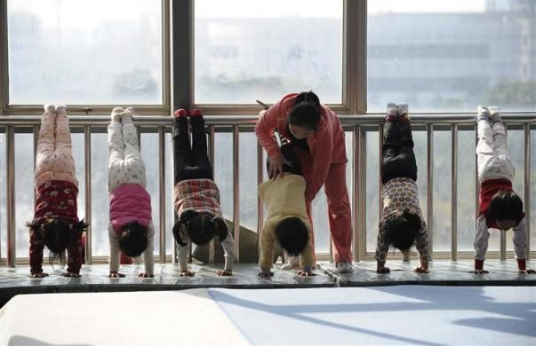 A coach gives instructions to a child during a training session at the gymnastics hall of a sports school in Jiaxing, Zhejiang province, China, December 17, 2011.  REUTERS/Stringer