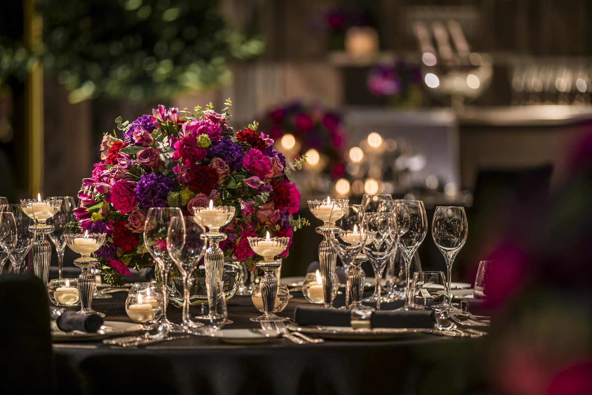 수많은 캔들과 함게 어우러진 퍼플, 마젠타 그리고 어두운 레드컬러의 조합의 특별한 웨딩센터피스. 니콜라이버그만에서 보여질 수 있는 당신만의 특별한 컬러와 디자인을 연출합니다.  Low and round wedding centerpieces using mauve and purple tones of vintage rose, lysianthus, alstromaeria, carnations with pops of green blooms for point. Arranged with cream colored candles.