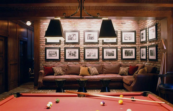 Who says the male environment has to be totally neutral and devoid of traditional flair? The muted brick and red tones in the billiard room add just enough color for those shy of a bolder palette. The soft leather sectional supplies the perfect place to plop down to have a beer and watch the game after a rousing round of pool