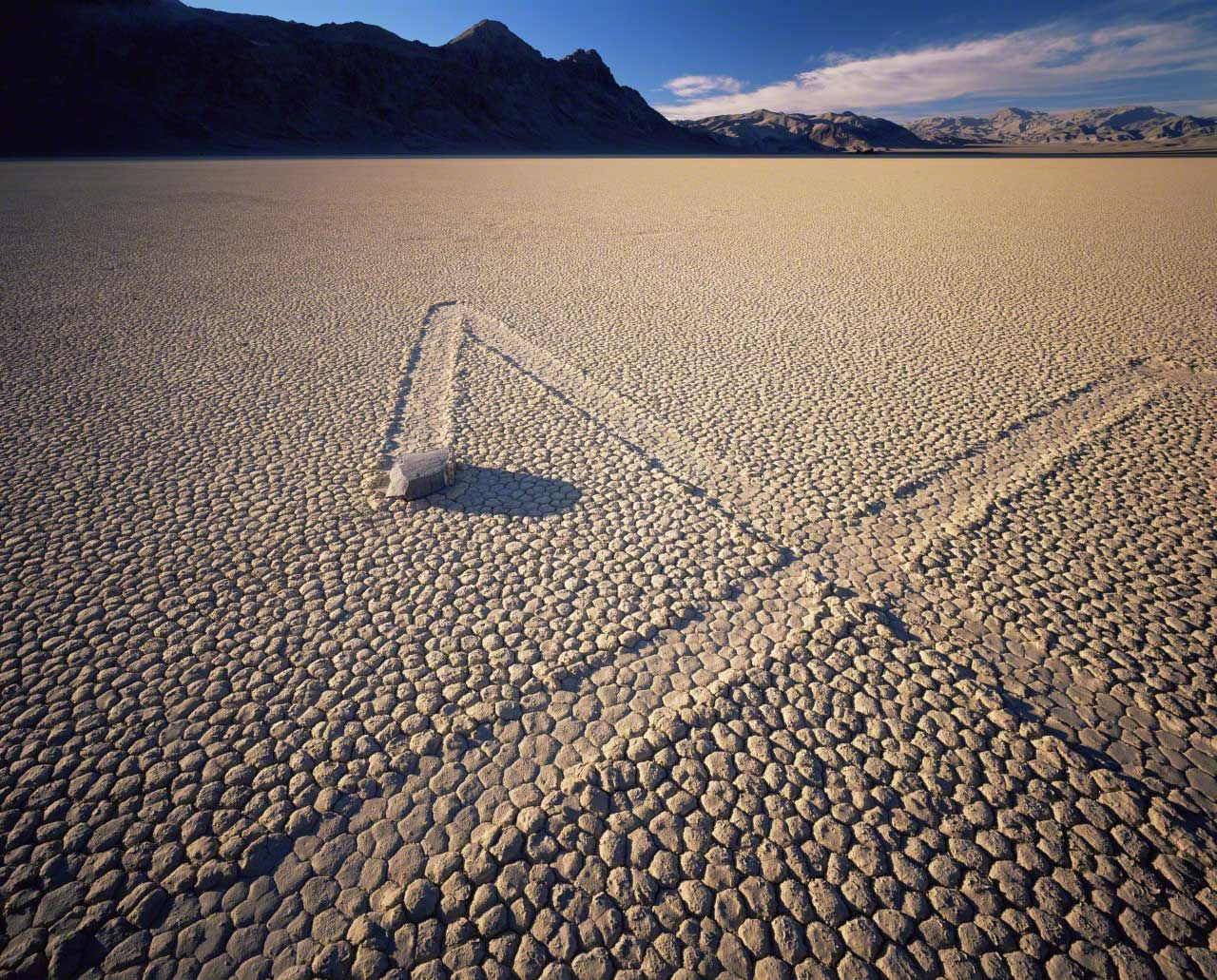California, USA --- Boulder with zig-zag trails across a dry lake bed, sunset, Ubehebe Peak in distance, The Racetrack Playa, Death Valley National Park, California --- Image by © Jack Dykinga/Nature Picture Library/Corbis