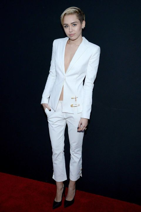 Miley Cyrus in a Versace suit on the American Music Awards red carpet. See all of the singer's wild looks.