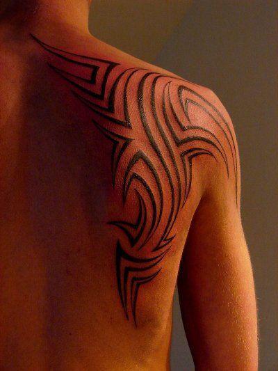 Shoulder tattoos for men man embedding a tribal tattoo for Tribal shoulder blade tattoos