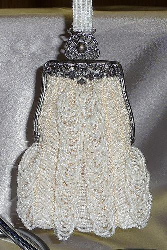 Antique filigree purse frame holding a bridal wristlet purse.