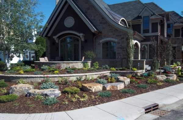 Elegant Beautiful Corner Lot Landscaping With Formal Stone Walls Are Interplanted  With A Shrub And Mulch Rock