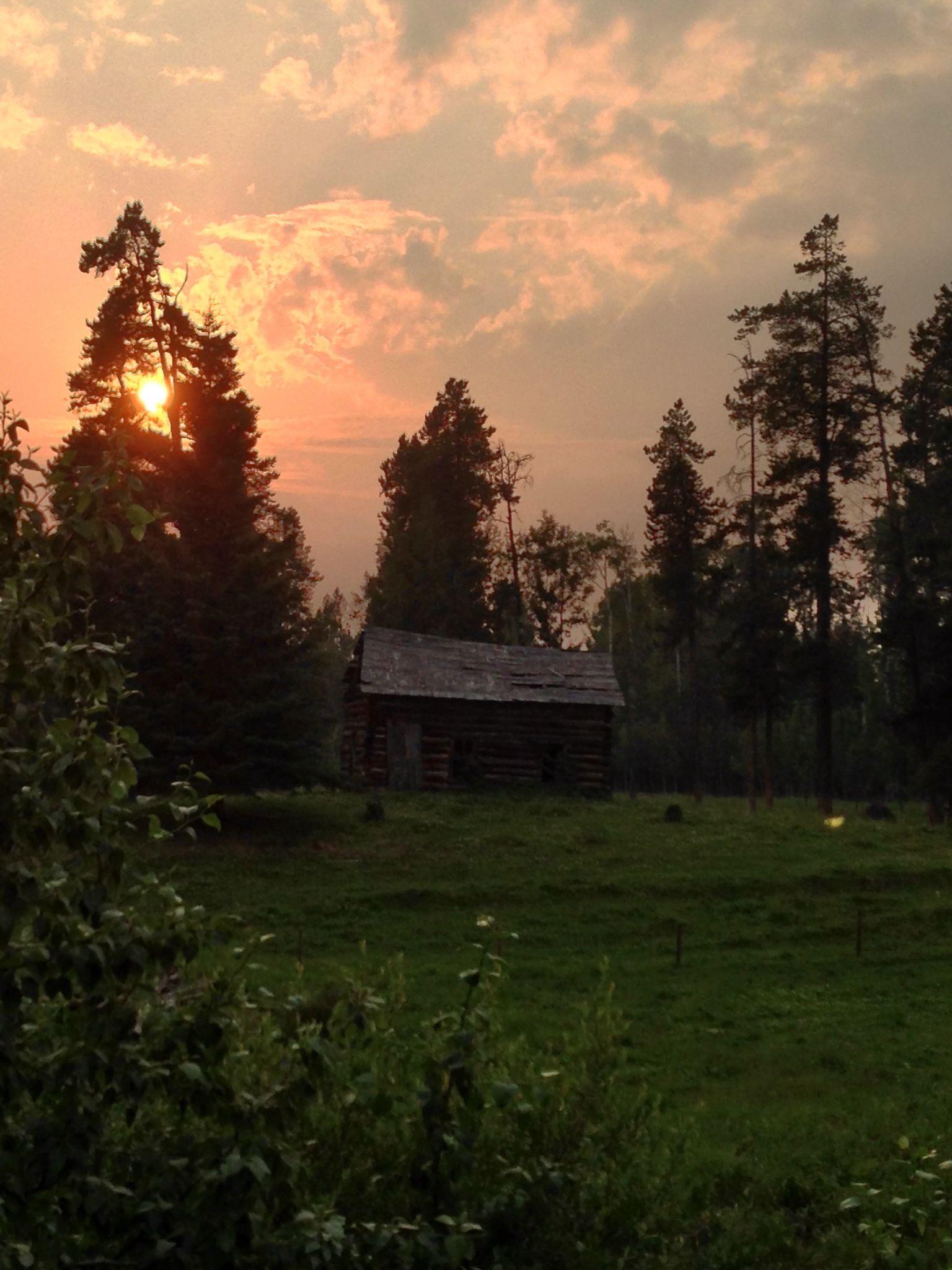 Allen family homestead log house. Forest fire smoke on horizon.
