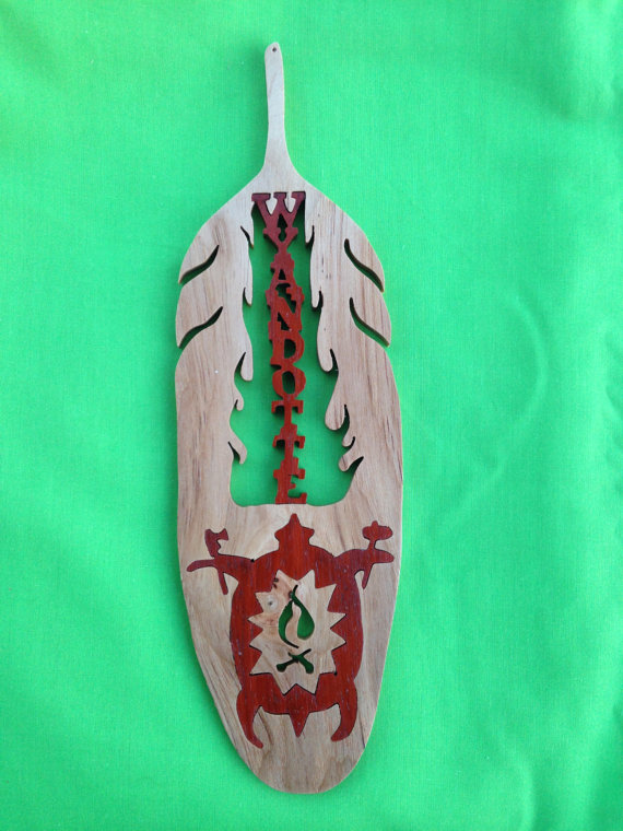 An inlaid wooden feather, approximately 9 inches long, cut with a scroll saw from Paduak and Maple and then sprayed with lacquer.