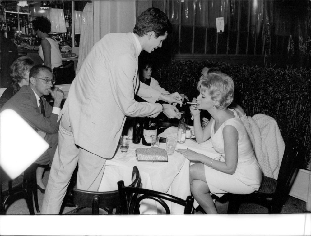 Vintage photo of Anthony Perkins lights a cigarette for woman. - Audrey Hepburn and Mel Ferrer in the back