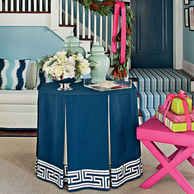 A Skirted Table In A Foyer Is Topped With Ginger Jars And A Lush  Arrangement Of