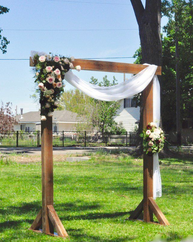 Outdoor wedding ceremony arch idea - wooden arch with greenery and white fabric  {Rustique Rentals & Event Design}