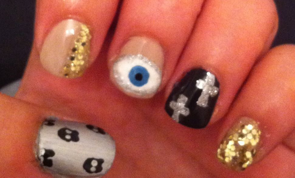 Mini skulls, evil eye, nude nails, gold glitter, nail polish, cross nails, nail art.