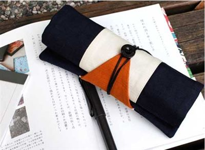 This beautifully decorated roll-up pencil case features a chic red and white design, and also makes use of a wrap-around string that fastens with a button, which is used to roll the pencil pouch back together.