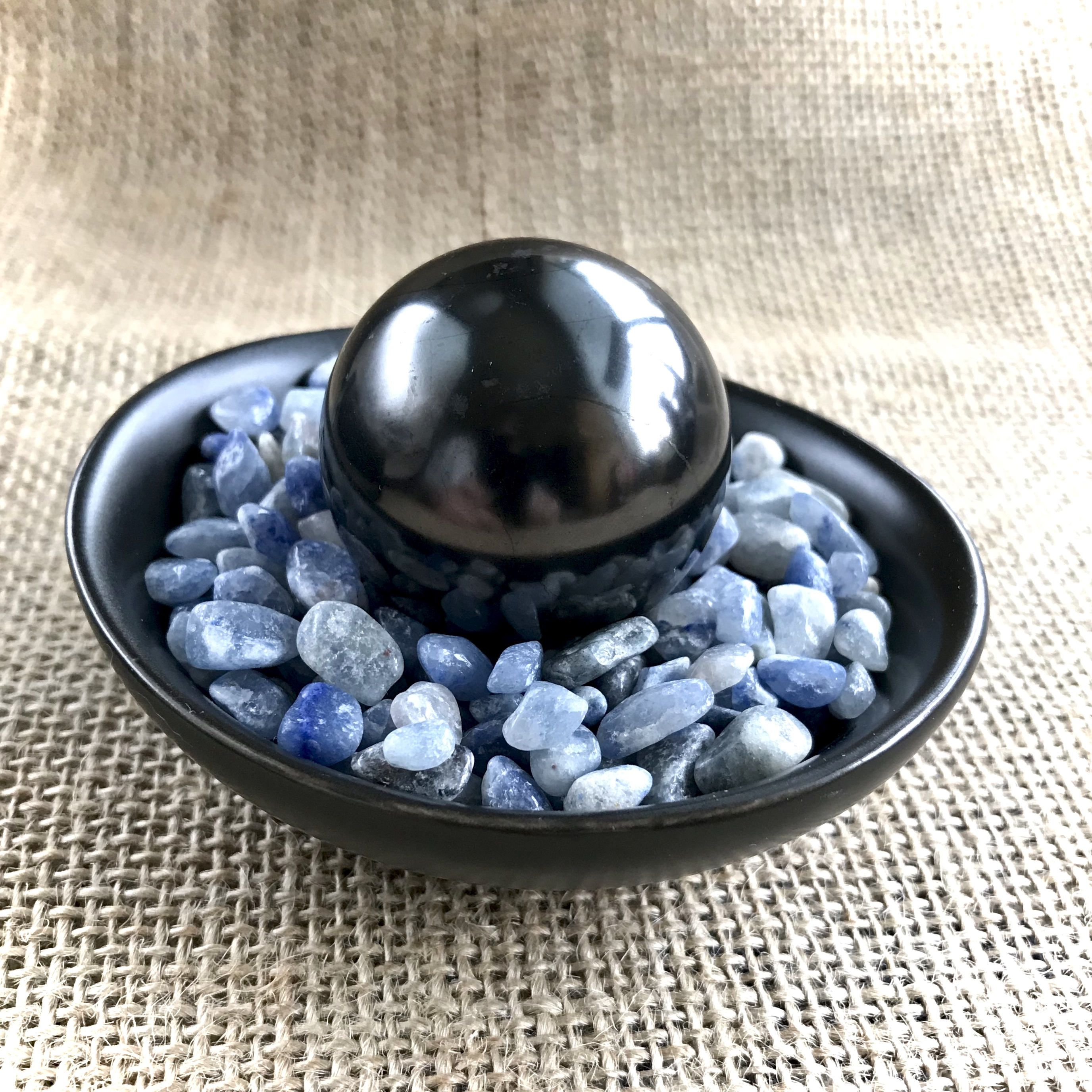small shungite sphere on bed of tiny tumbled blue aventurine