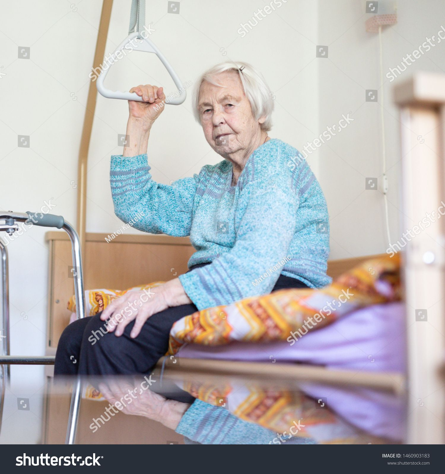 Elderly 96 years old woman sitting on medical bed in