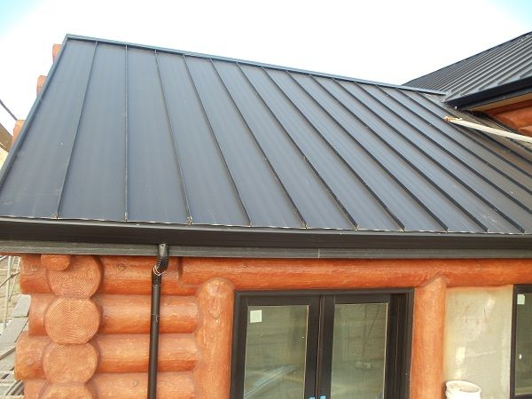 Standing Seam Metal Roofing System Installed On A Log