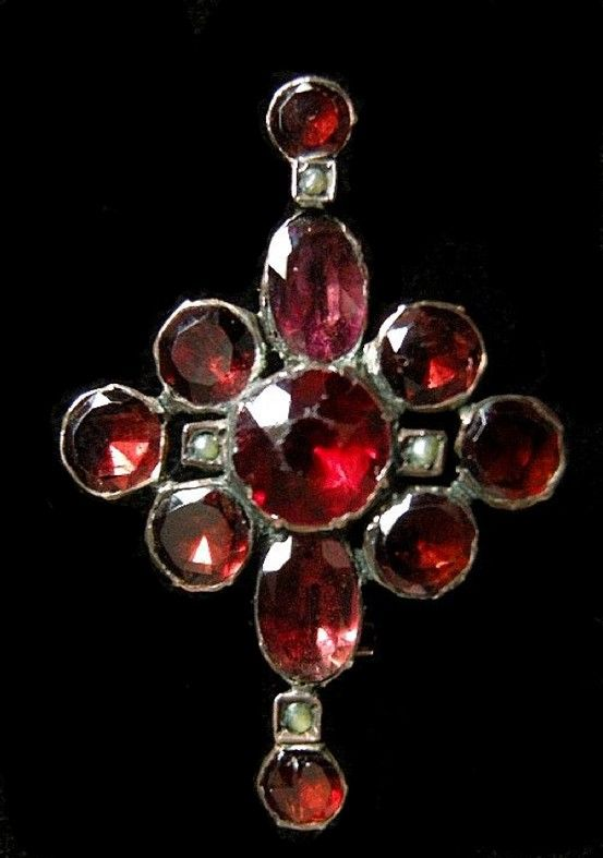 A Georgian fichu ( lace pin ) . Made of 9ct gold, of bar design centered by a central cluster, the cluster set with a red paste surrounded by foiled flat cut garnets and seed pearls with further seed pearls and garnets set into the bar. Silver pin. Circa 1820