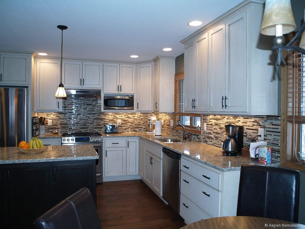 white kitchen cabinets, black island, nice back splash, lighting