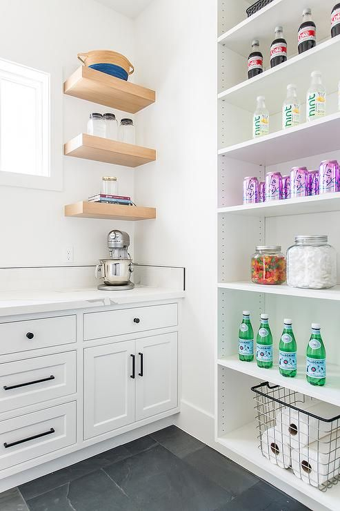 a gray slate floor contrasts a white kitchen pantry