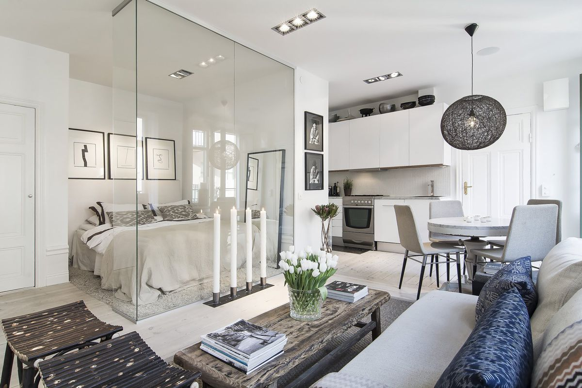 This compact apartment in the heart of stockholm measures 366 square feet the open plan design and the glass wall between the bedroom and living space