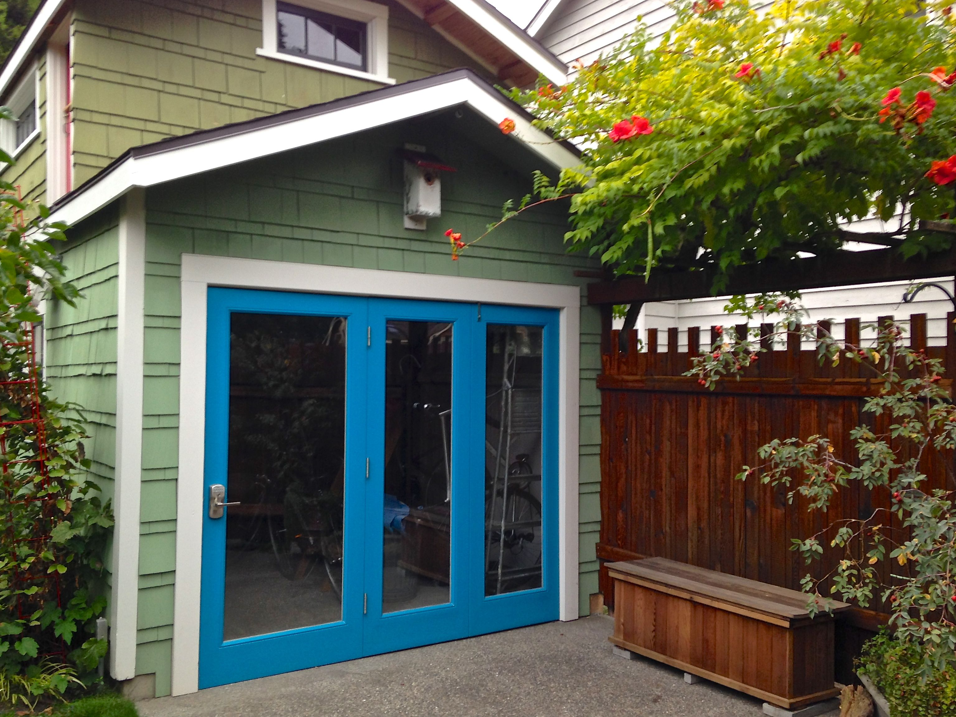 Folding glass doors on garage allow for easy access and