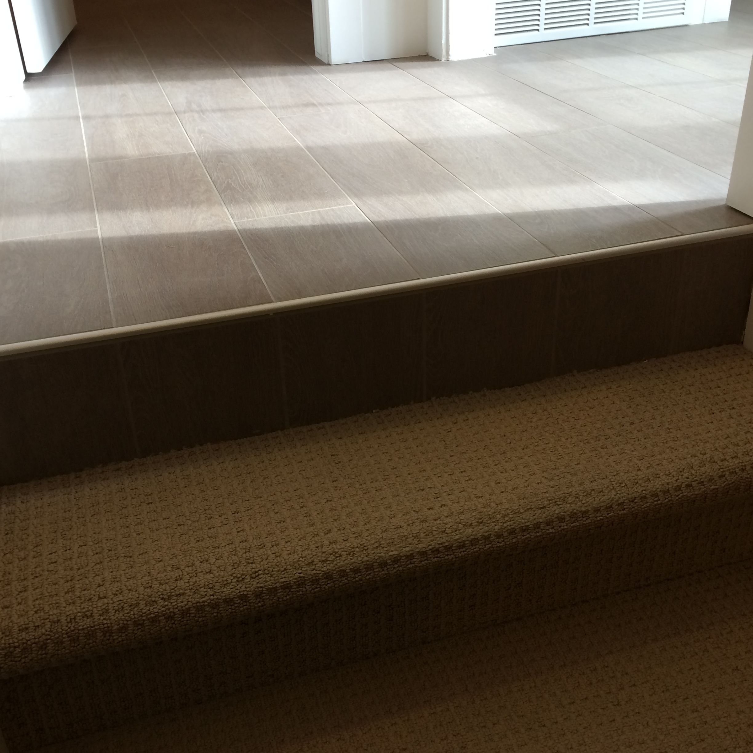 Wood Floor Tile With Metal End Cap At Top Of Staircase | Tile To Wood Stair Transition | Builder Grade | Upstairs | Residential | Laminate | Entryway
