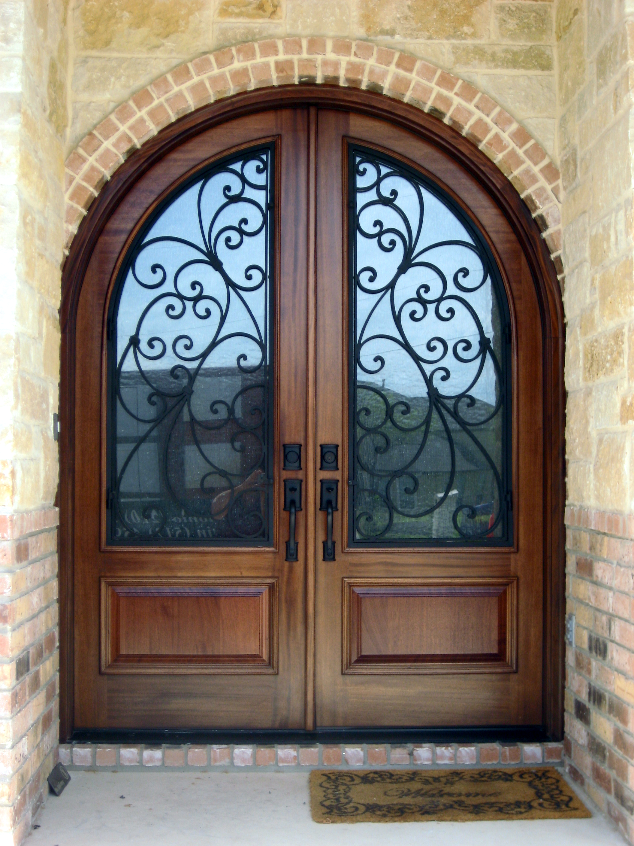 This Elegant Home Received An Upgrade With This Round Top Wood And Wrought Iron Double Door Front Door And Entry Wood Doors Wood Front Doors Front Entry Doors