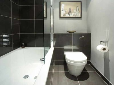 Small Hotel Bathroom No Tub Grey Tiles And White Walls Small Bathroom White Bathroom Designs Monochrome Bathroom
