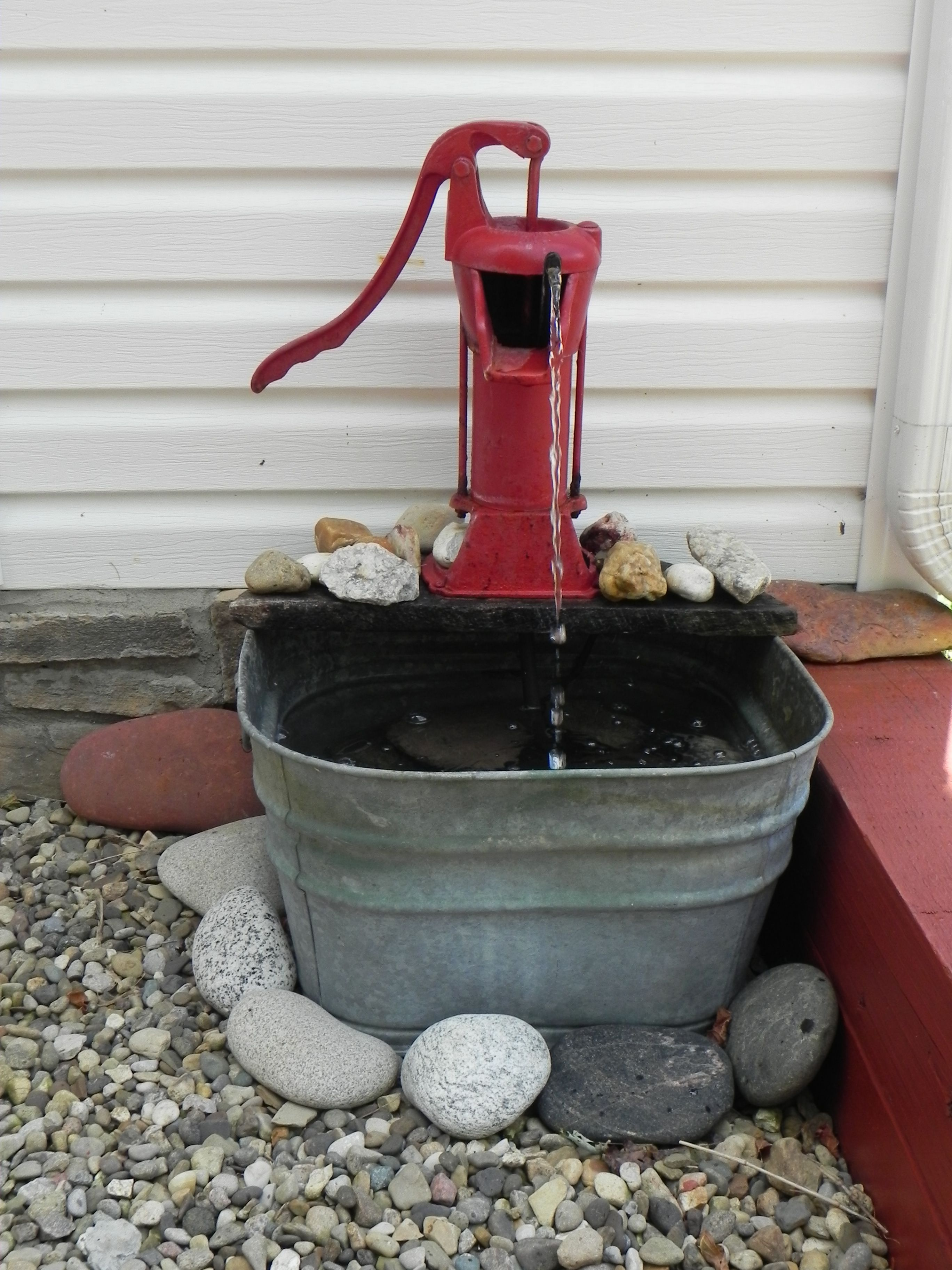 old water well pump and a tub makes a unique water feature