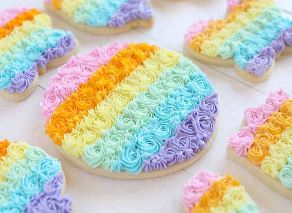 These sugar cookies are decorated with piped rainbow ...