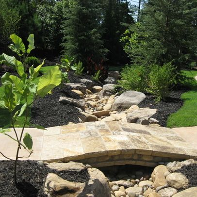 landscaping a drainage ditch with rocks, boulders and stone bridge