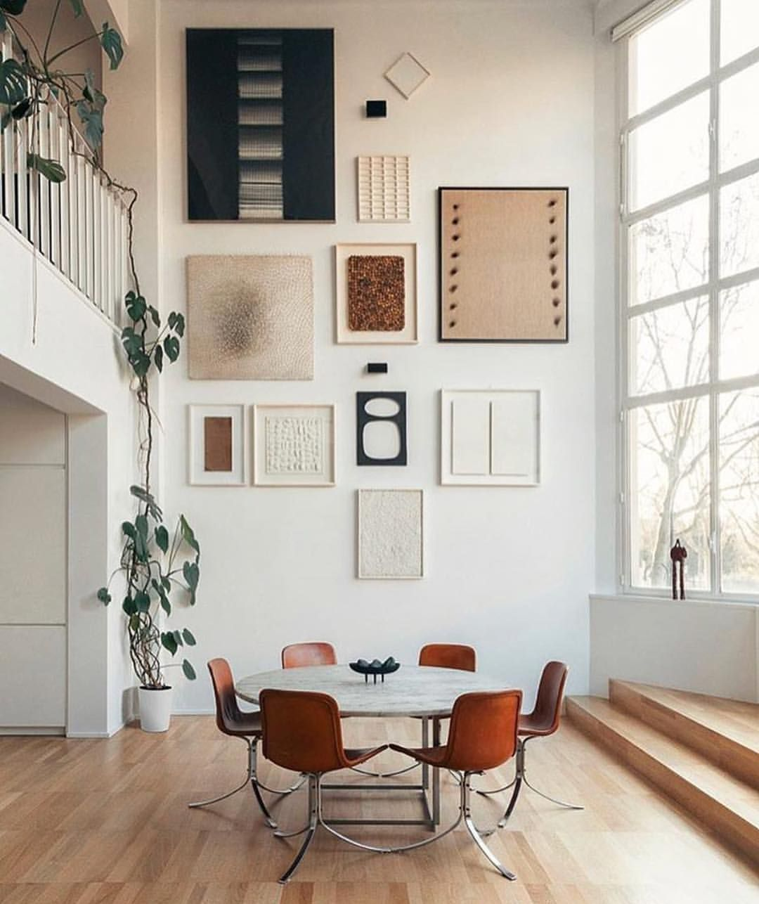 Gallery wall art over dining table with extra tall ceilings
