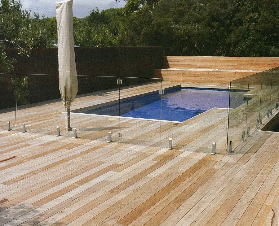 Outdoor swimming pool design idea with wooden deck and for Designer glass pool fencing