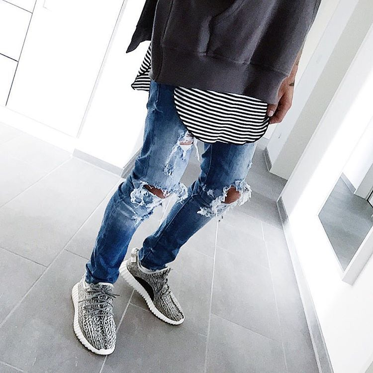 edgy look. Light wash ripped jeans with an oversized black white and grey top.