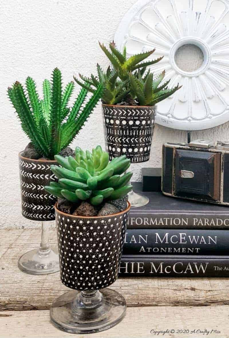 Add a touch of class and whimsy to your décor with these gorgeous DIY broken wine glass stem planters. #DIYPlanters #WineglassRepurpose #ACraftyMix #ClassicDecor #BlackandWhite #UniquePlanters