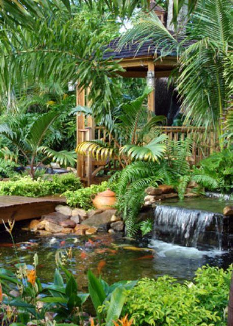 A Koi Pond With Waterfall And Bridge That Leads To Gazebo