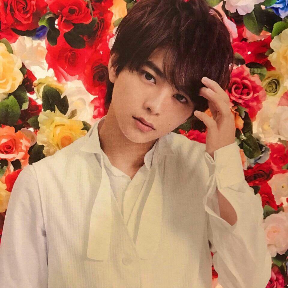 花がいっぱいの背景と写る佐藤勝利
