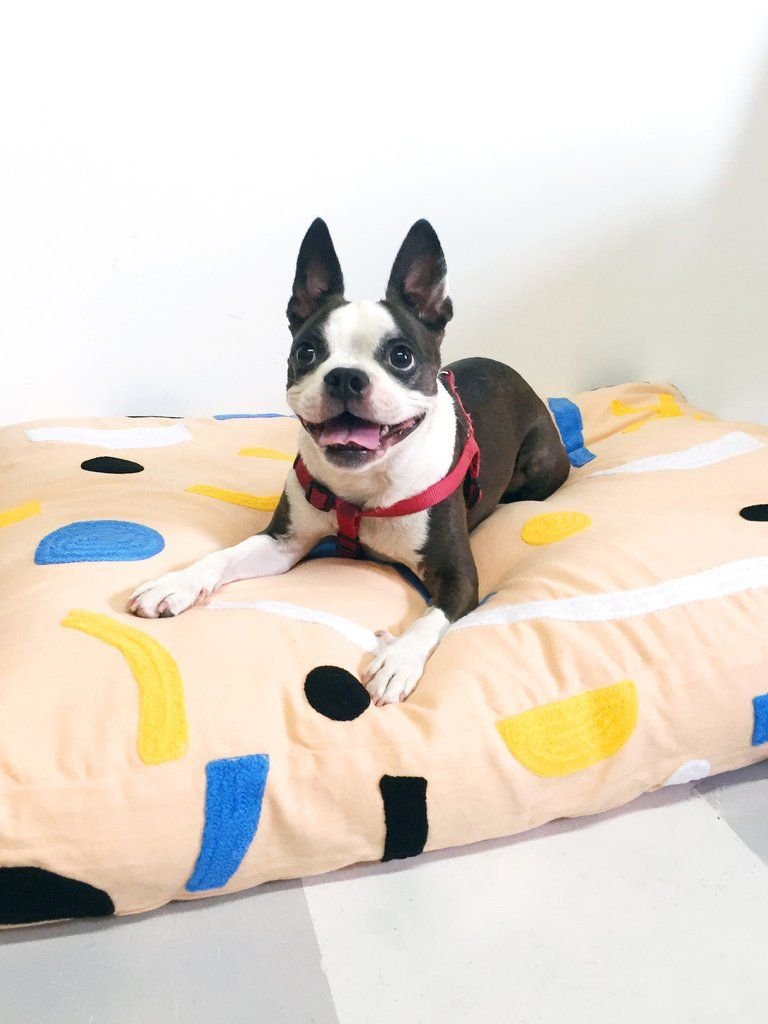 Embroidered peach dog bed in yellow, blue, black and white paper ...