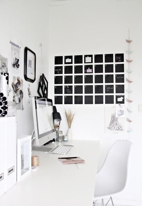 White and black home office design, really simple and clean. Great planner on the wall.