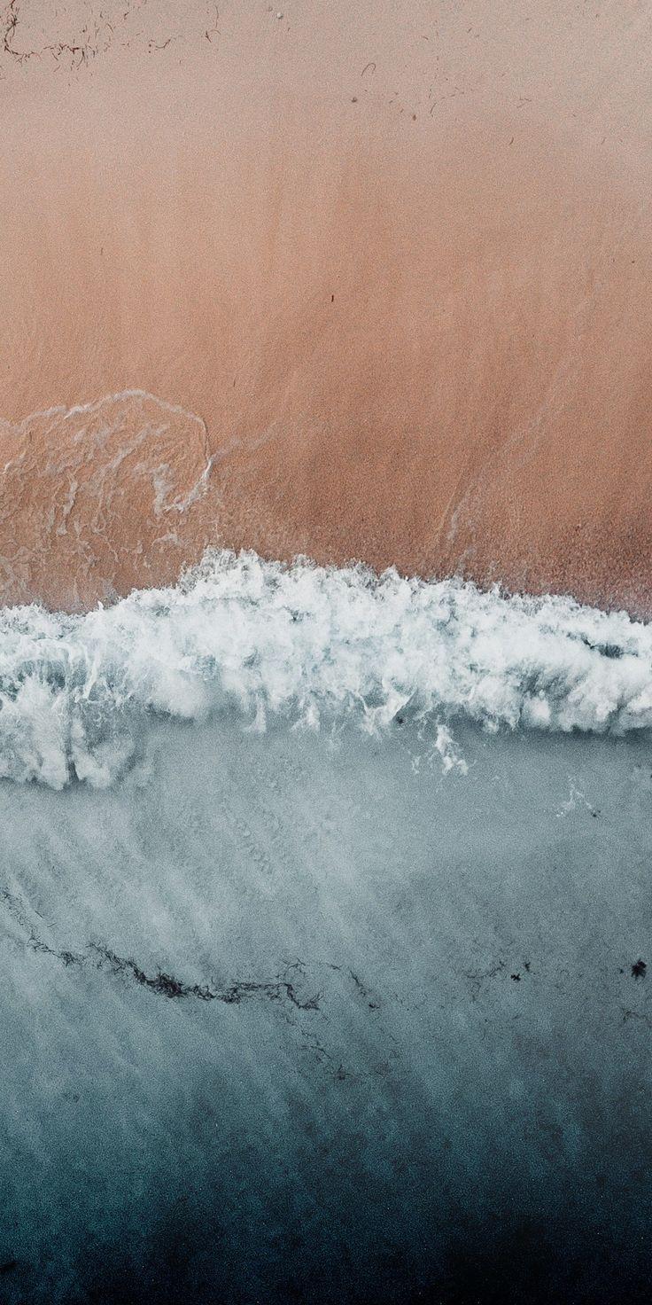 Playa de arena oxidada con olas desde arriba color óxido