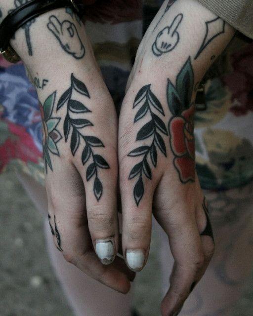 Photo of Deux branches noires avec des feuilles de tatouage encrées sur les deux pouces