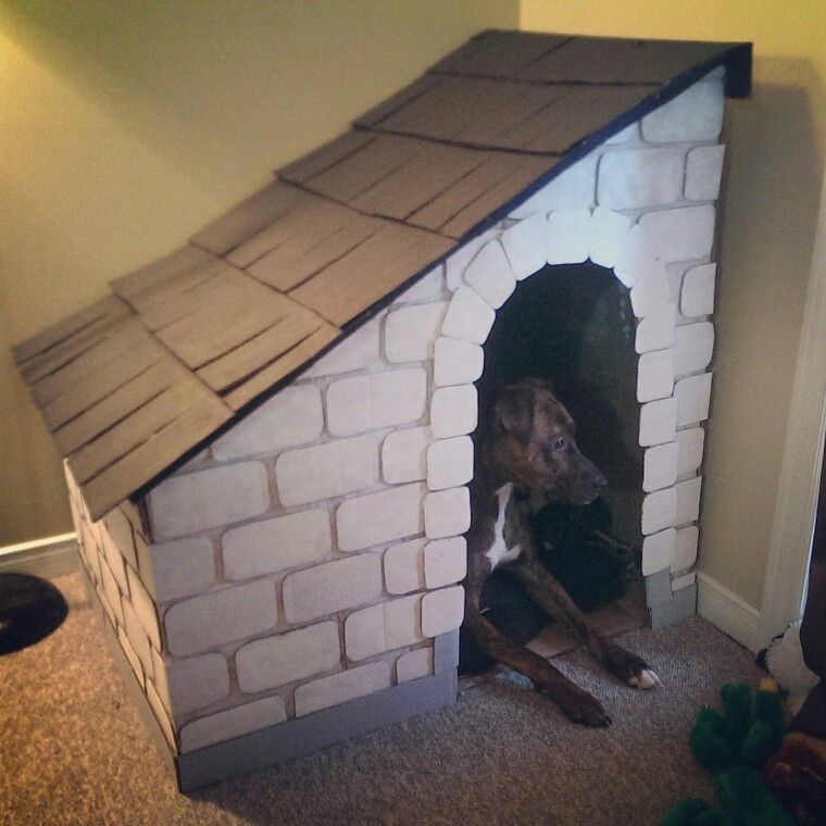 DIY cardboard dog house. Everything was cut from cardboard moving boxes. Used masking tape to put together the structure. Cut out and painted the bricks, shingles, trim etc. And hot glued the pieces in place.