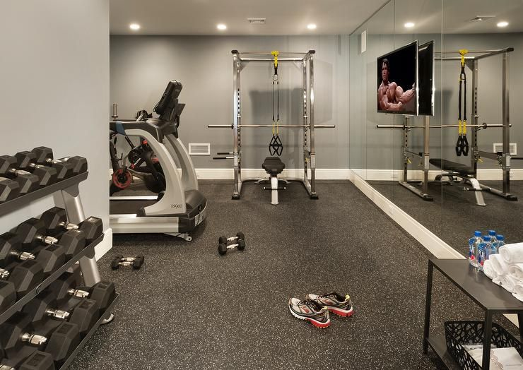 Basement gym features a mirrored accent wall lined with a flat