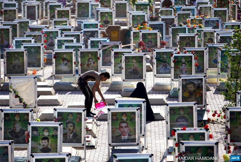 IRAQ, NAJAF : Iraqi Shiites clean the grave of a relative at one of the world's biggest cemeteries in the holy city of Najaf, on July 29, 2014, during the Eid al-Fitr celebrations marking the end of the Muslim fasting month of Ramadan. AFP PHOTO / HAIDAR HAMDANI